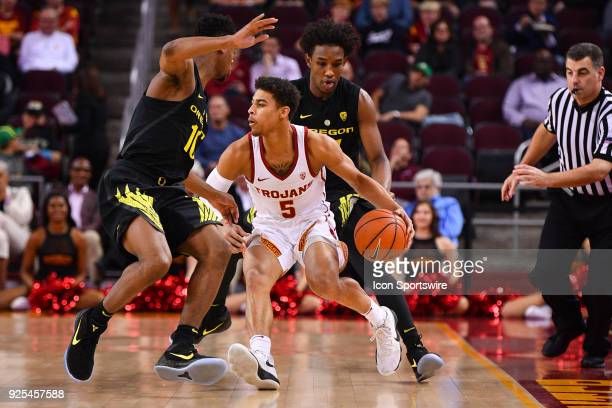 USC guard Derryck Thornton is trapped by Oregon forward Troy Brown and forward Abu Kigab during a college basketball game between the Oregon Ducks...