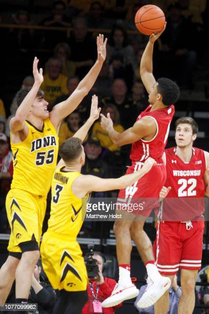 Guard D'Mitrik Trice of the Wisconsin Badgers takes a shot in the first half against guard Jordan Bohannon and forward Luka Garza of the Iowa...