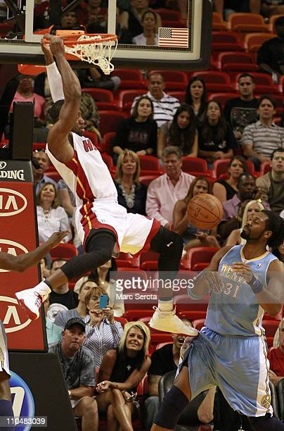 Guard Dwyane Wade of the Miami Heat dunks over Center Nene of the Denver Nuggets at American Airlines Arena on March 19 2011 in Miami Florida NOTE TO...