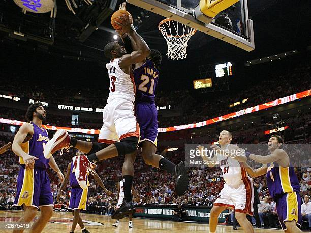 Guard Dwyane Wade of the Miami Heat is defended by forward Ronnie Turiaf guard Sasha Vujacic and forward Luke Walton of the Los Angeles Lakers as...