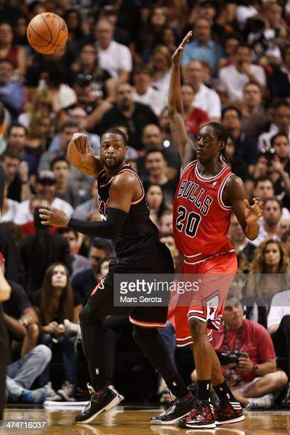 Guard Dwyane Wade of the Miami Heat is defended by Guard Tony Snell of the Chicago Bulls at AmericanAirlines Arena on February 23 2014 in Miami...
