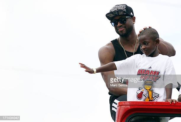 Guard Dwyane Wade of the Miami Heat rides a bus with his son during the Championship victory parade on the streets on June 24 2013 in Miami Florida...