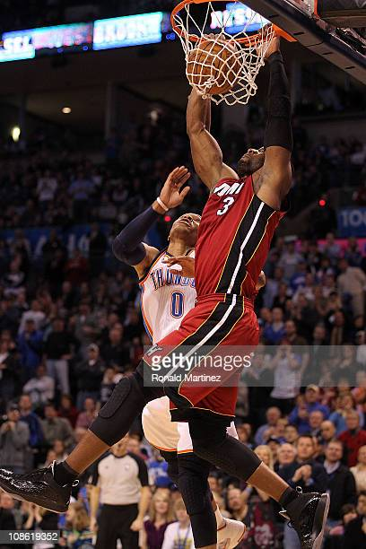 Guard Dwyane Wade of the Miami Heat takes a shot against Russell Westbrook of the Oklahoma City Thunder at Ford Center on January 30 2011 in Oklahoma...