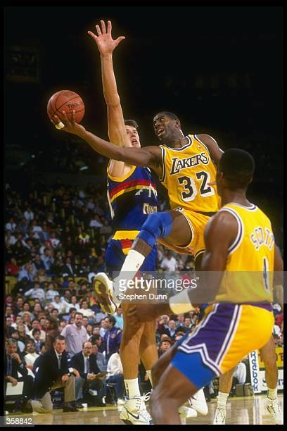 Guard Earvin Johnson of the Los Angeles Lakers moves the ball during a game against the Denver Nuggets at McNichols Arena in Denver Colorado