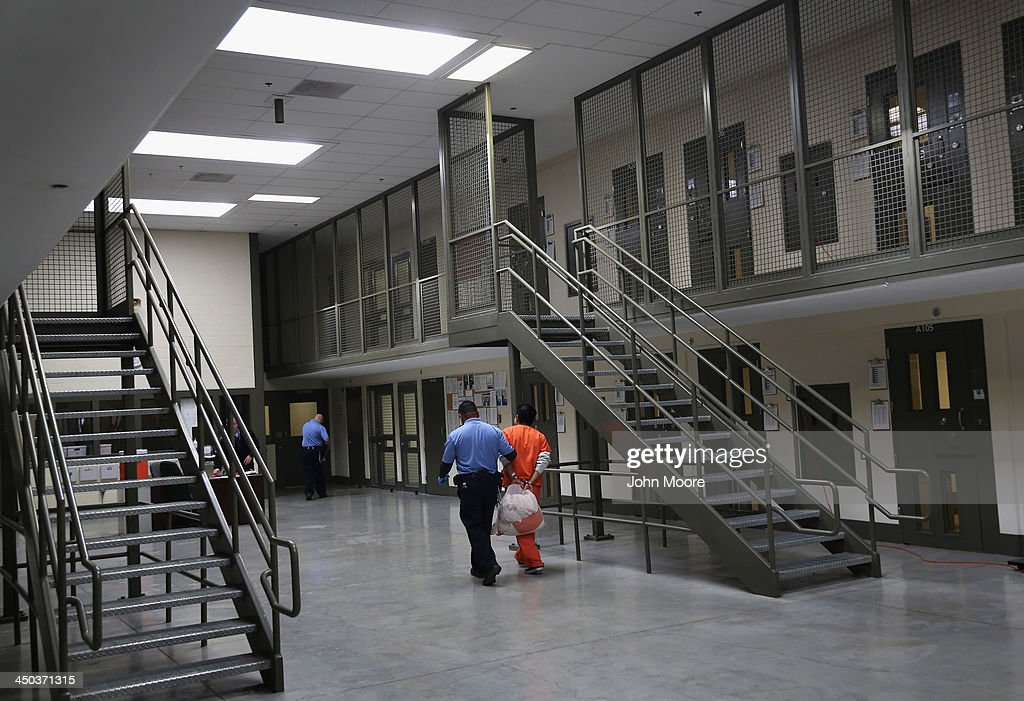 A guard escorts an immigrant detainee from his 'segregation cell' back into the general population at the Adelanto Detention Facility on November 15, 2013 in Adelanto, California. Most detainees in segregation cells are sent there for fighting with other immigrants, according to guards. The facility, the largest and newest Immigration and Customs Enforcement (ICE), detention center in California, houses an average of 1,100 immigrants in custody pending a decision in their immigration cases or awaiting deportation. The average stay for a detainee is 29 days. The facility is managed by the private GEO Group. ICE detains an average of 33,000 undocumented immigrants in more than 400 facilities nationwide.