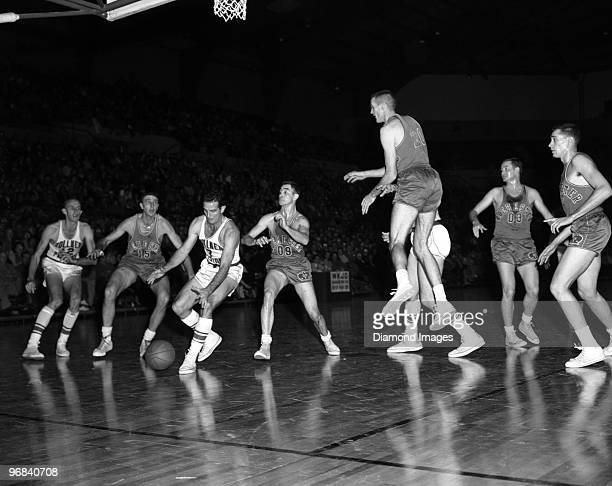 Guard Frankie Brian of the Fort Wayne Zollner Pistons reaches for the ball while being guarded by Bobby Wanzer of the Rochester Royals during a game...