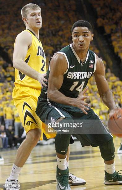 Guard Gary Harris of the Michigan State Spartans brings the ball down the court during the first half past guard Josh Oglesby of the Iowa Hawkeyes on...