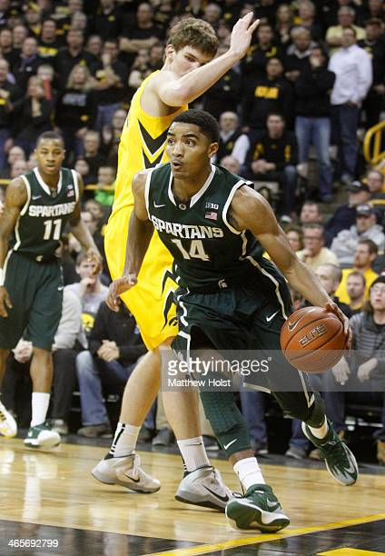 Guard Gary Harris of the Michigan State Spartans drives to the basket during the second half past center Adam Woodbury of the Iowa Hawkeyes on...