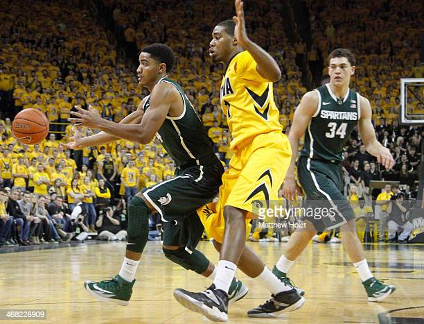 Guard Gary Harris of the Michigan State Spartans passes the ball away during the first half in front of forward Melsahn Basabe of the Iowa Hawkeyes...