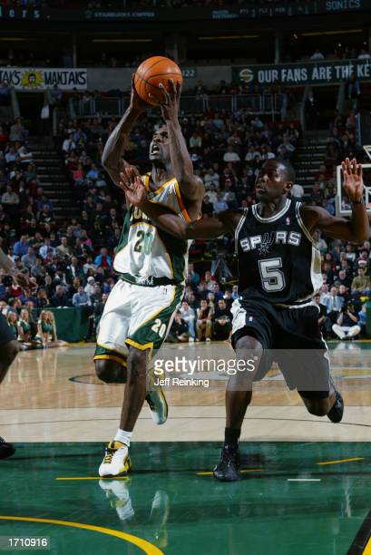 Guard Gary Payton of the Seattle Sonics drives past guard Anthony Goldwire of the San Antonio Spurs during the game at Key Arena on December 18, 2002...