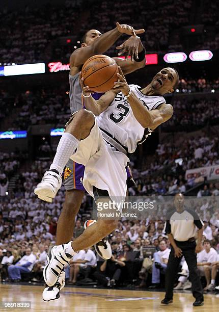 Guard George Hill of the San Antonio Spurs is fouled by Channing Frye of the Phoenix Suns in Game Three of the Western Conference Semifinals during...