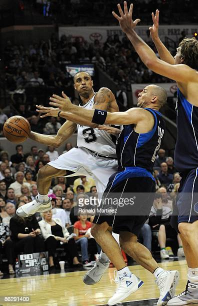 Guard George Hill of the San Antonio Spurs passes the ball against Jason Kidd and Dirk Nowitzki of the Dallas Mavericks in Game Five of the Western...
