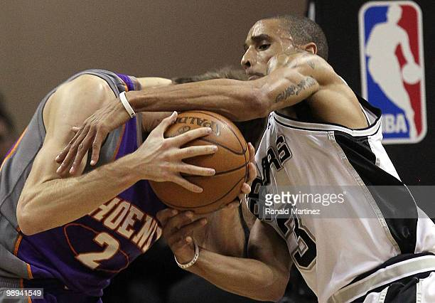 Guard George Hill of the San Antonio Spurs reaches for the ball against Goran Dragic of the Phoenix Suns in Game Four of the Western Conference...