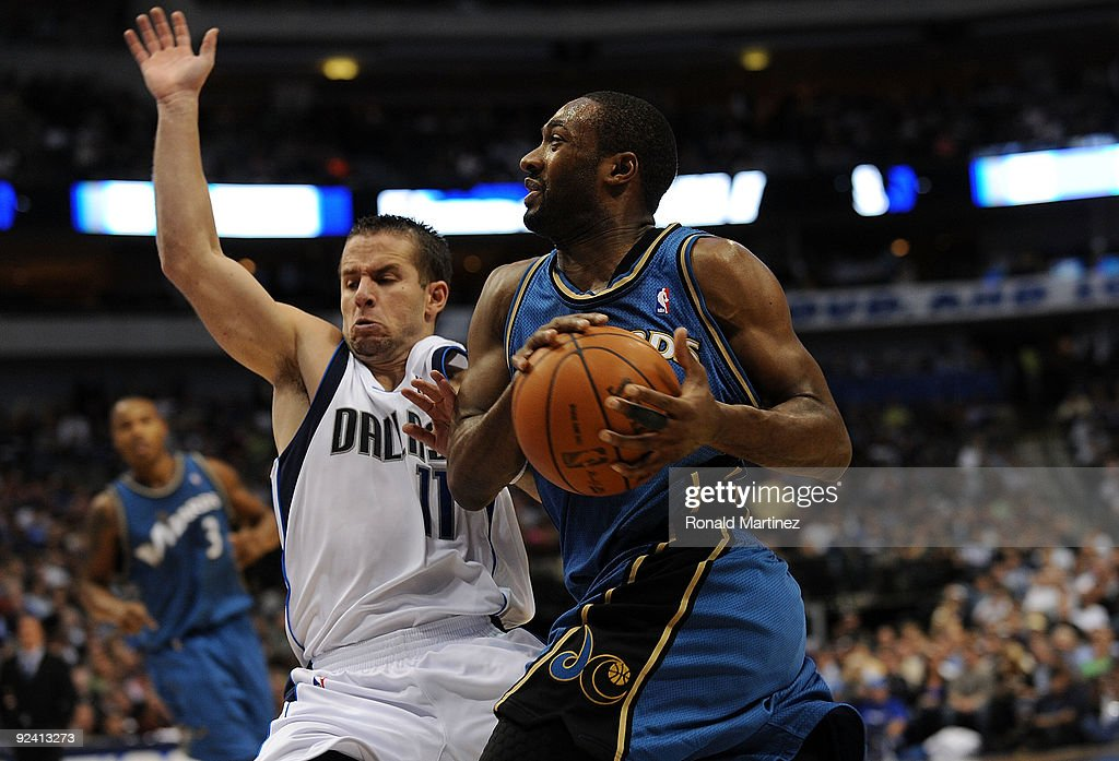 Guard Gilbert Arenas #0 of the Washington Wizards is fouled by Jose Juan Barea #11 of the Dallas Mavericks during the season opener on October 27, 2009 at American Airlines Center in Dallas, Texas.