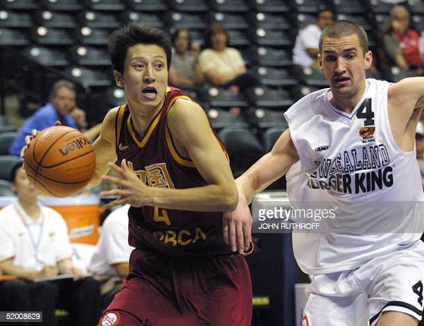 Guard Guo Shioiang of China takes the ball downcourt as guard Mark Dickel of New Zealand defends 04 September 2002 at the Conseco Fieldhouse in...