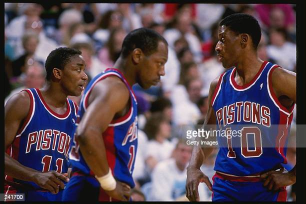 Guard Isiah Thomas left forward Dennis Rodman right and forward Vinnie Johnson of the Detroit Pistons talk to each other during a game Mandatory...