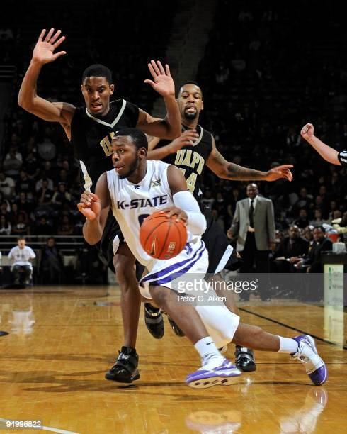 Guard Jacob Pullen of the Kansas State Wildcats drives around pressure from defenders of the Arkansas-Pine Bluff Lions in the second half on December...
