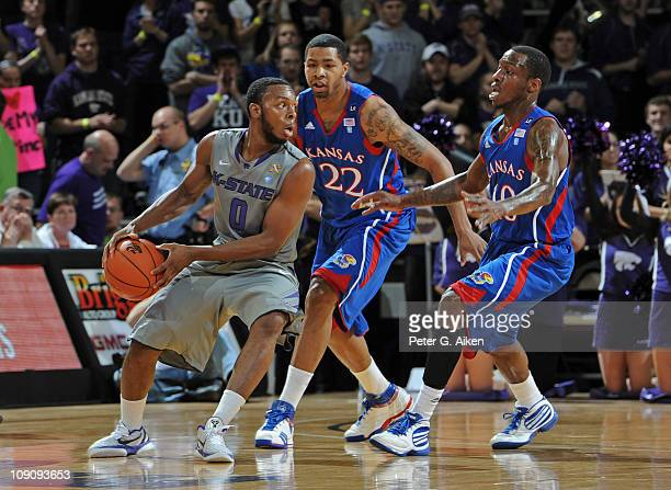 Guard Jacob Pullen of the Kansas State Wildcats looks to make a pass against pressure from defenders Marcus Morris and Tyshawn Taylor of the Kansas...