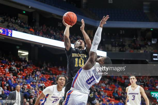 Guard Jacoby Ross of the Alabama State Hornets goes up for a shot over the top of guard Marcus Dickinson of the Boise State Broncos during second...