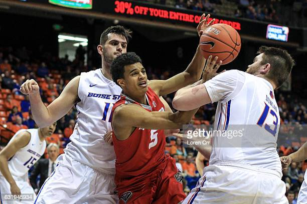 Guard Jalen Harris of the New Mexico Lobos gets caught in the defense of forward Zach Haney and forward Nick Duncan of the Boise State Broncos during...
