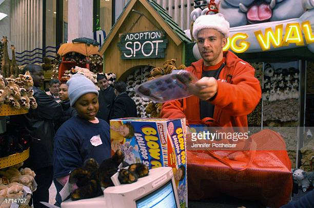Guard Jason Kidd of the New Jersey Nets hands out a toy during a Holiday visit to FAO Swartz Toystore on December 20 2002 in New York New York NOTE...