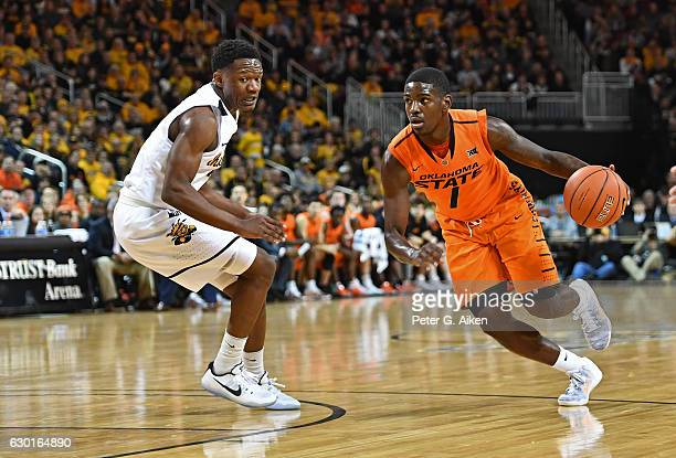 Guard Jawun Evans of the Oklahoma State Cowboys drives with the ball against guard Daishon Smith of the Wichita State Shockers during the first half...