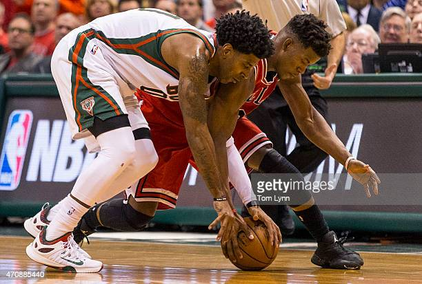 Guard Jimmy Butler of the Chicago Bulls and guard OJ Mayo of the Milwaukee Bucks battle for a loose ball in the fourth quarter of game three during...