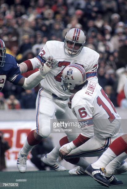 Guard John Hannah of the New England Patriots tries to protect quarterback Jim Plunkett during a game on October 20 1974 against the Buffalo Bills at...