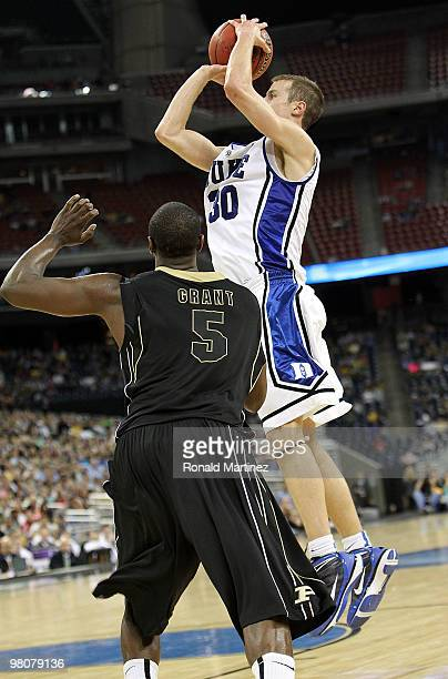 Guard Jon Scheyer of the Duke Blue Devils takes a shot against Keaton Grant of the Purdue Boilermakers during the south regional semifinal of the...