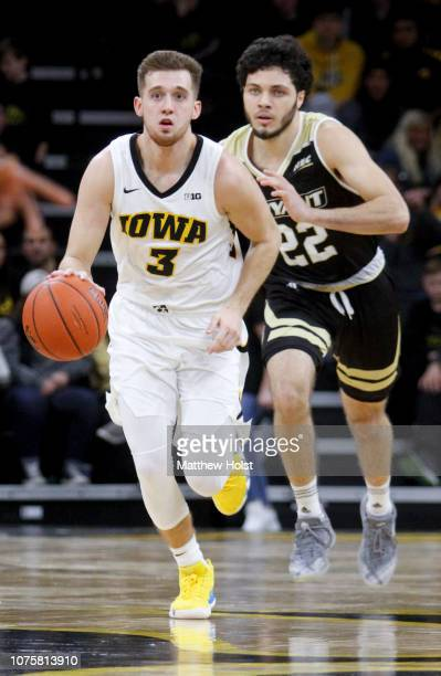 Guard Jordan Bohannon of the Iowa Hawkeyes brings the ball down the court in the second half in front of guard Joe Kasperzyk of the Bryant Bulldogs...