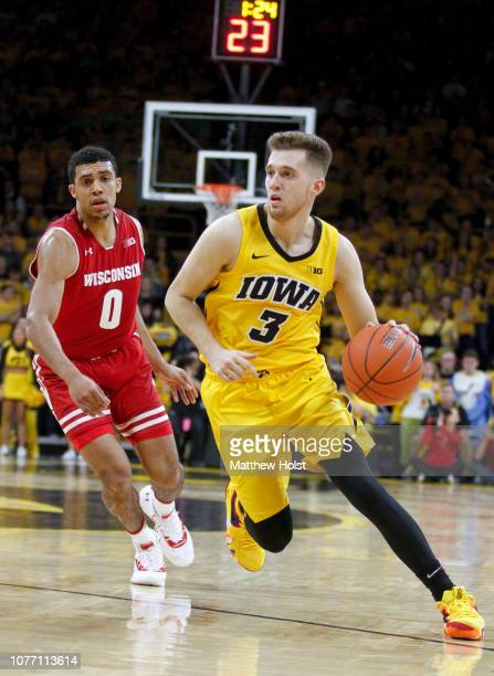 Guard Jordan Bohannon of the Iowa Hawkeyes brings the ball down the court in the second half in front of guard D'Mitrik Trice of the Wisconsin...