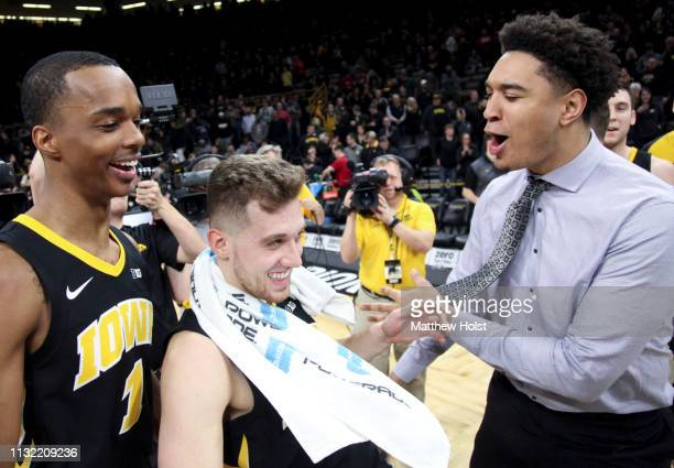 Guard Jordan Bohannon of the Iowa Hawkeyes celebrates with guard Maishe Dailer and Cordell Pemsl following the overtime win against the Indiana...