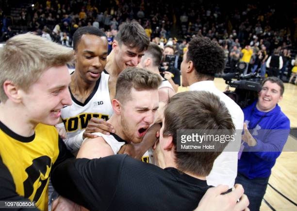Guard Jordan Bohannon of the Iowa Hawkeyes celebrates with teammates after hitting the winning shot to defeat the Northwestern Wildcats on February...