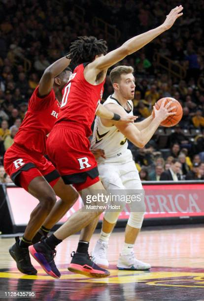 Guard Jordan Bohannon of the Iowa Hawkeyes drives in the second half against guard Geo Baker and forward Eugene Omoruyi of the Rutgers Scarlet...