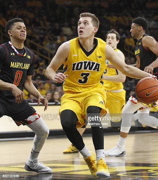 Guard Jordan Bohannon of the Iowa Hawkeyes drives to the basket in front of guard Anthony Cowan of the Maryland Terrapins in the second half on...