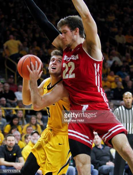 Guard Jordan Bohannon of the Iowa Hawkeyes goes to the basket in the second half in front of forward Ethan Happ of the Wisconsin Badgers on November...