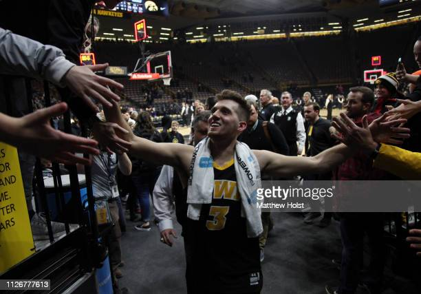 Guard Jordan Bohannon of the Iowa Hawkeyes greets fans while leaving the court following the overtime win against the Indiana Hoosiers on February 22...
