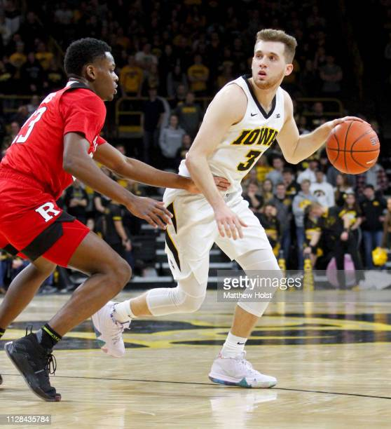 Guard Jordan Bohannon of the Iowa Hawkeyes moves the ball down the court in the second half against guard Montz Mathis of the Rutgers Scarlet Knights...