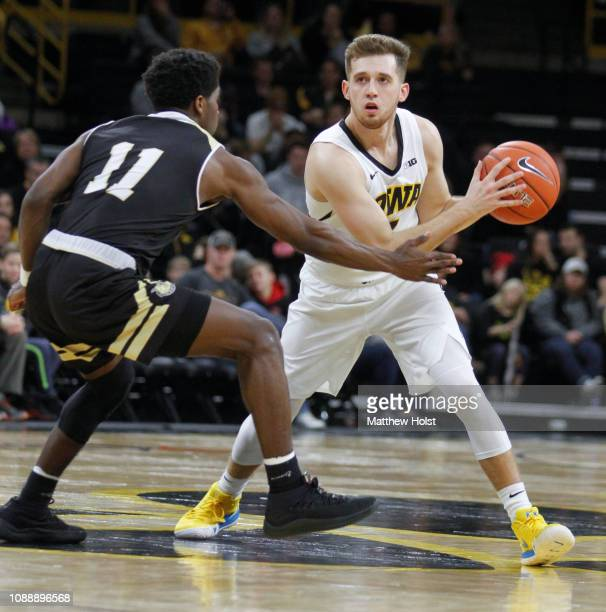 Guard Jordan Bohannon of the Iowa Hawkeyes moves the ball in the second half against guard Adam Grant of the Bryant Bulldogs on December 29 2018 at...