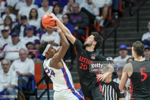 Guard Jordan Schakel of the San Diego State Aztecs blocks the shot of forward Abu Kigab of the Boise State Broncos during second-half action at...