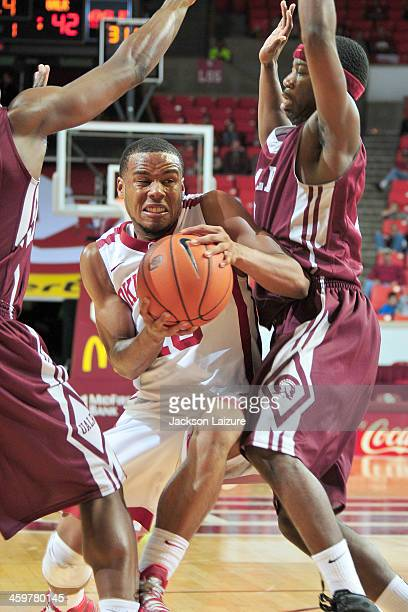 Guard Jordan Woodard of the Oklahoma Sooners drives the ball while being defended by guard Josh Hagins of the University of Arkansas-Little Rock...