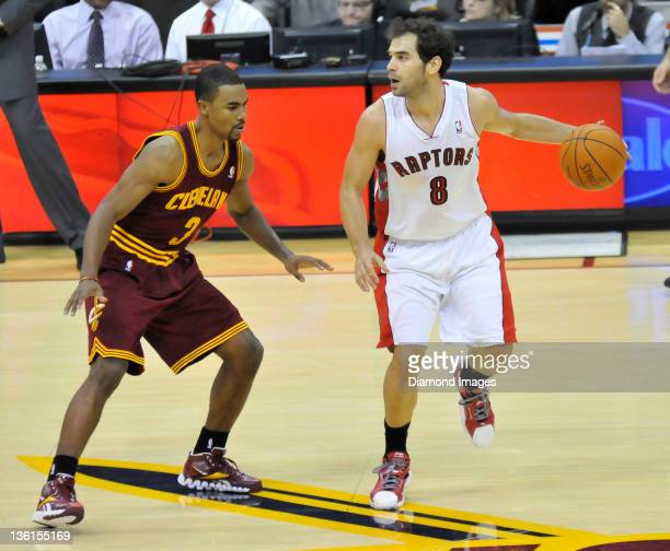 Guard Jose Calderon of the Toronto Raptors dribbles the ball away from guard Ramon Sessions of the Cleveland Cavaliers during a game with the...