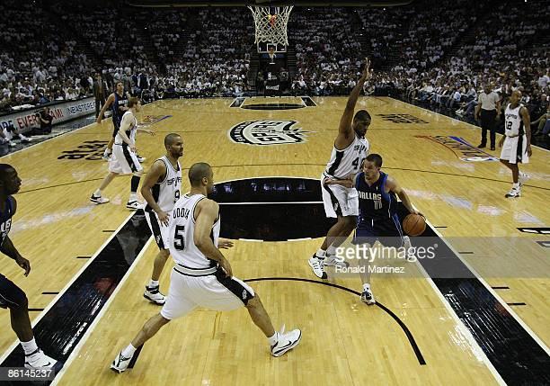 Guard Jose Juan Barea of the Dallas Mavericks drives the hoop against Kurt Thomas Ime Udoka and Tony Parker of the San Antonio Spurs in Game One of...