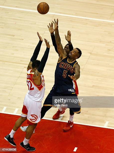 Guard JR Smith of the Cleveland Cavaliers shoots over forward Mike Scott and guard Dennis Schroder of the Atlanta Hawks in Game Two of the Eastern...