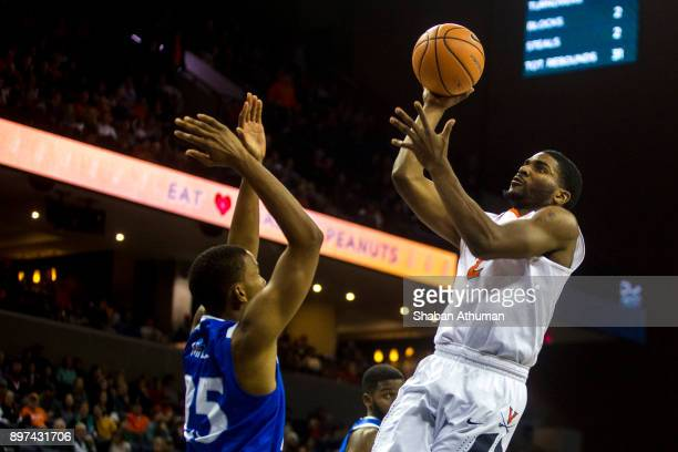 Guard Justice Bartley of the University of Virginia Cavalier goest up for two as he is defended by Guard Akim Mitchell of the Hampton University...