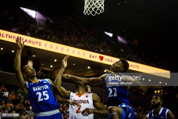 Guard Justice Bartley of the University of Virginia Cavalier is hit in the face by Forward Trevond Barnes of the Hampton University Pirates at John...