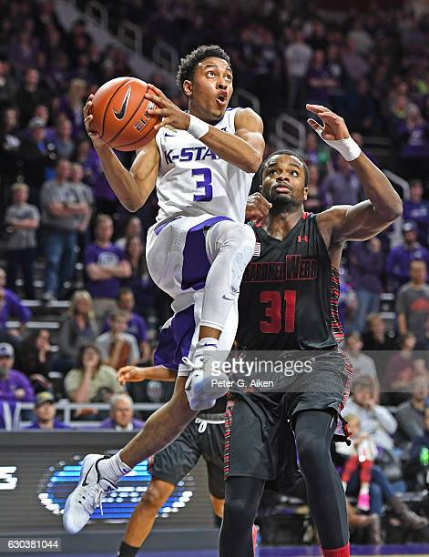 Guard Kamau Stokes of the Kansas State Wildcats drives to the basket past center L'Hassane Niangane of the GardnerWebb Bulldogs during the second...