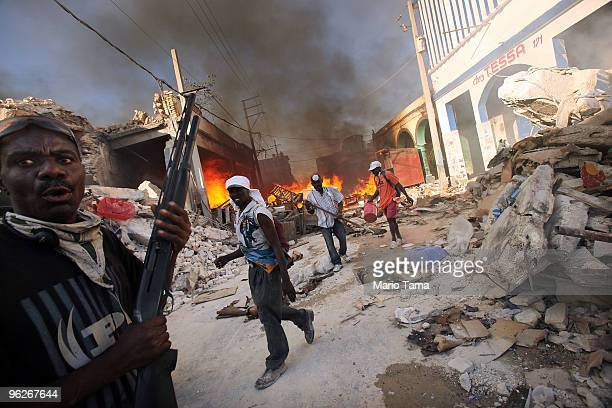 Guard keeps watch as people rescue goods from an approaching fire at one of several suspicious blazes in the Iron Market area January 29, 2010 in...