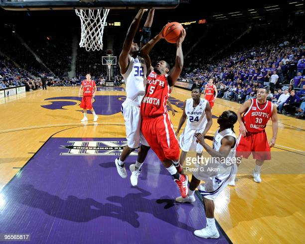 Guard Kendall Cutler of the South Dakota Coyotes drives to the basket against pressure from forward Jamar Samuels of the Kansas State Wildcats in the...