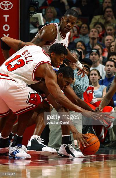 Guard Kendall Gill and forward Antonio Davis of the Chicago Bulls battle for a loose ball with forward Kurt Thomas of the New York Knicks during a...